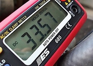 Photo 4: This inductive ammeter, which is clamped on the alternator's B+ output wire, indicates 33.57 amperes charging output.