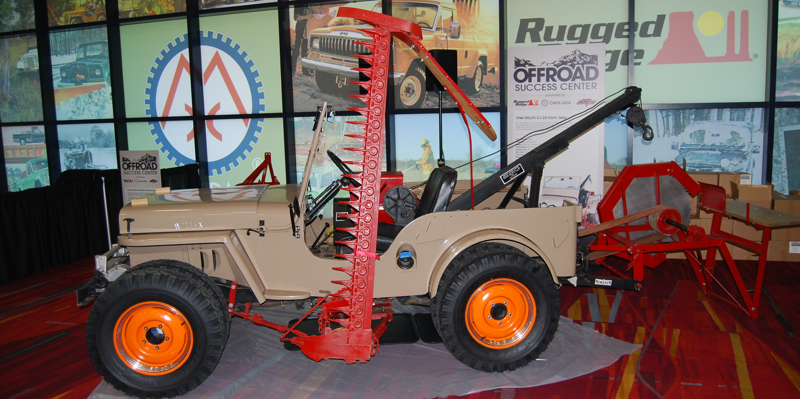 This Farm Jeep has a front PTO winch and an engine-driven air compressor. It also has a side arm mower bar on the driver's side.