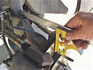 Photo 2: By comparing right- and left- hand side measurements, an adjustable carpenter's square will quickly reveal a bent strut or steering knuckle.